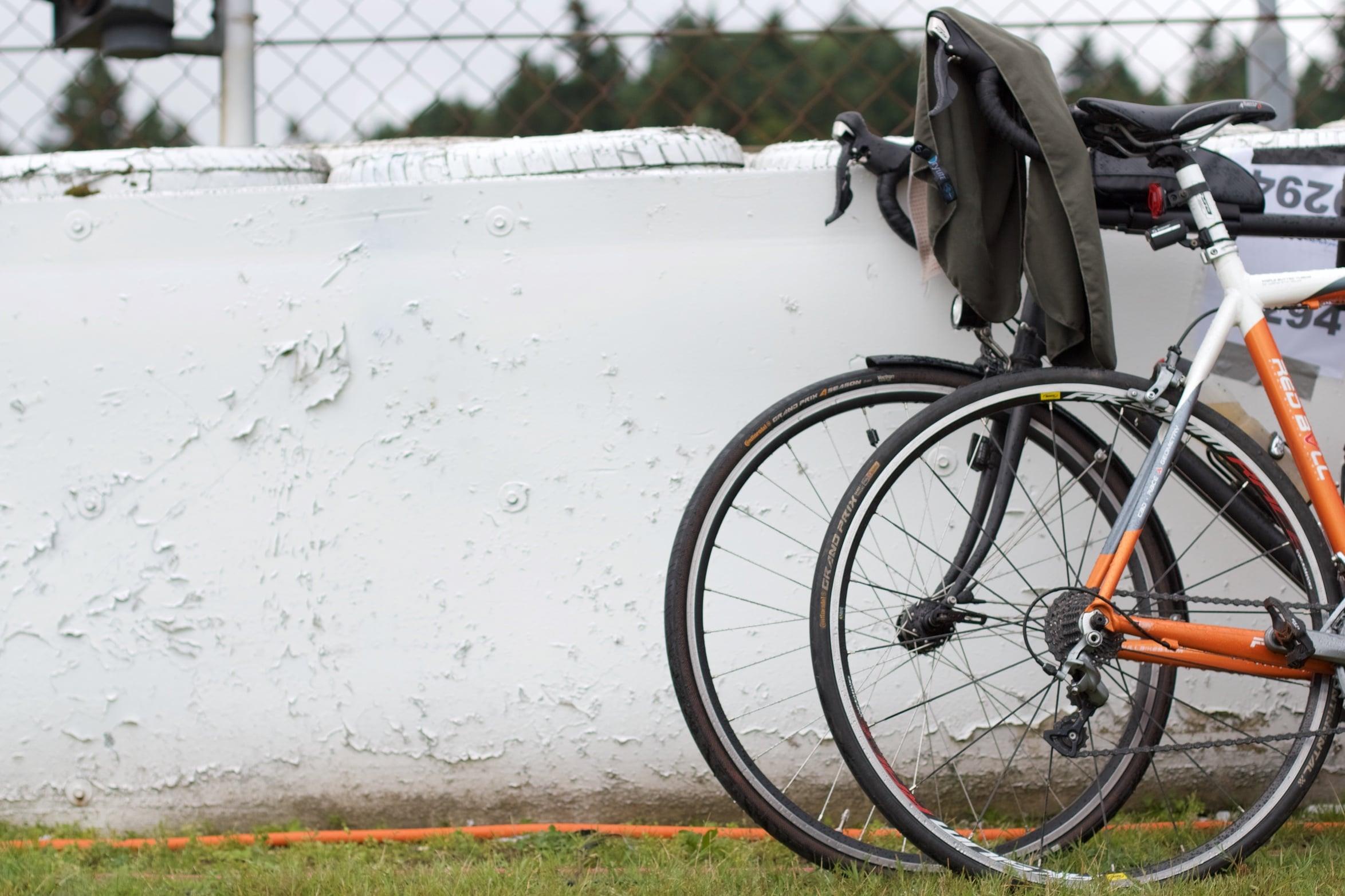 Ein Rennrad und ein Randonneur angelehnt an die mit Reifen gefüllte Streckenabsperrung hinter dem Grünstreifen