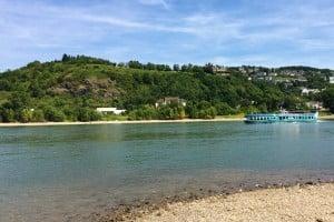 Rhein im Vordergrund, im Hintergrund kleine Berge. Auf dem Rhein fährt ein blaues Schiff, das einem Wal nachempfunden angemalt ist