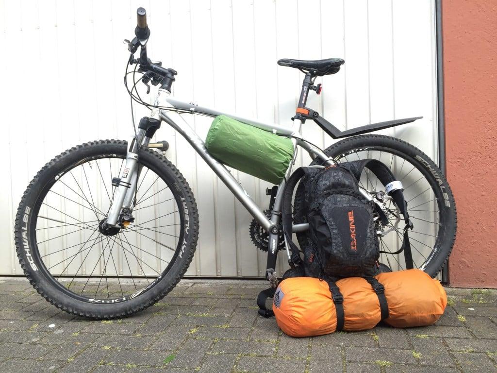 Hardtailmountainbike mit Isomatte im Rahmendreieck, davor ein Rucksack mit angehängtem eingepackten Zelt