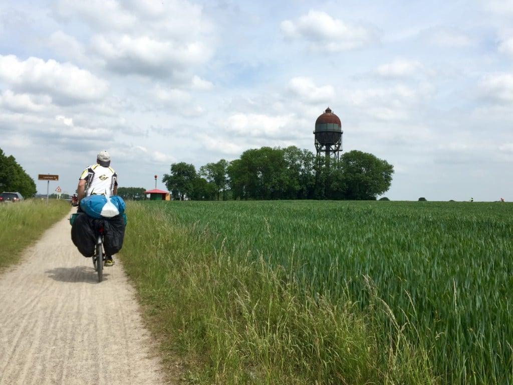Im linken Drittel ein bepackter Radfahrer auf einem Radweg, rechts Natur und ein eiförmiger Wasserspeicher