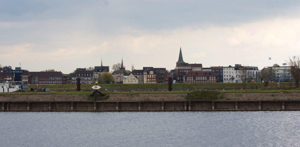 Häuserfront mit herausragendem Kirchturm im Hintergrund, im Vordergrund sind die Ruhr und die Abgrenzung zum kleinen Deich zu erkennen