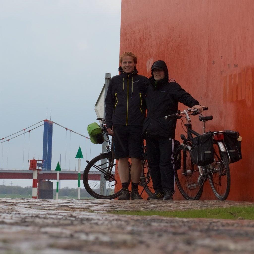 Zwei Radfahrer mit Fahrrädern hinter sich vor riesigem orangenen Klotz, links im Hintergrund eine Brücke