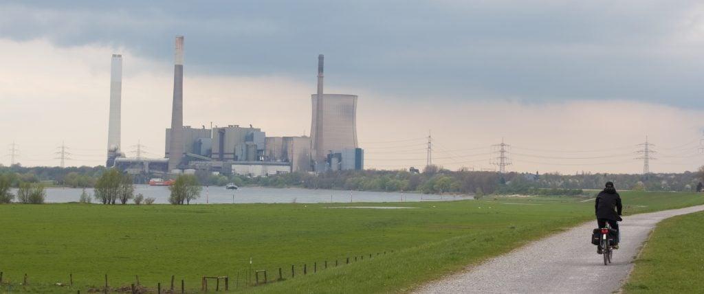 Im Hintergrund ist das große Kohlekraftwerk Steag sichtbar, im Vordergrund ein Deich mit viel grünem Rasen und einem Radfahrer auf einem Schotterweg