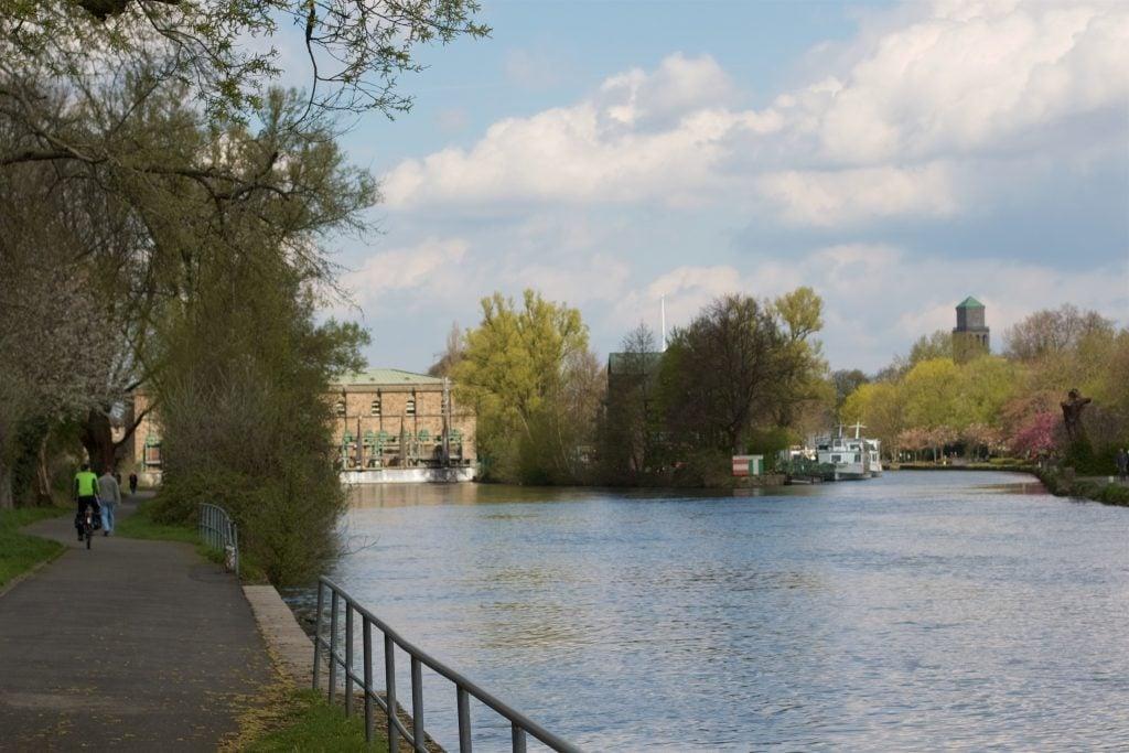 Recht ruhiges Wasser auf der rechten Seite mit einigen grünen Bäumen, im Hintergrund ragt ein Turm aus den Bäumen und kleine Boote und Schiffe sind erkennbar. Links ein Fußweg mit Radfahrer und Fußgänger.