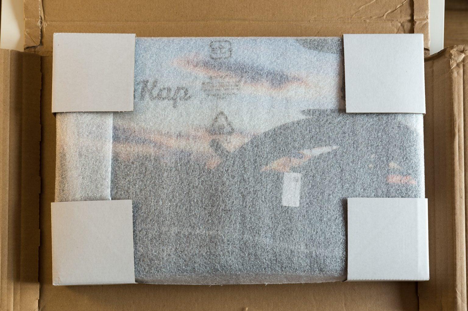 Zugeklapptes DIN-A3 Fotobuch mit der Vorderseite nach oben gerichtet in seiner Versandverpackung. Zum Schutz sind eine leichte Polsterhülle sowie Eckenschoner am Buch angebracht